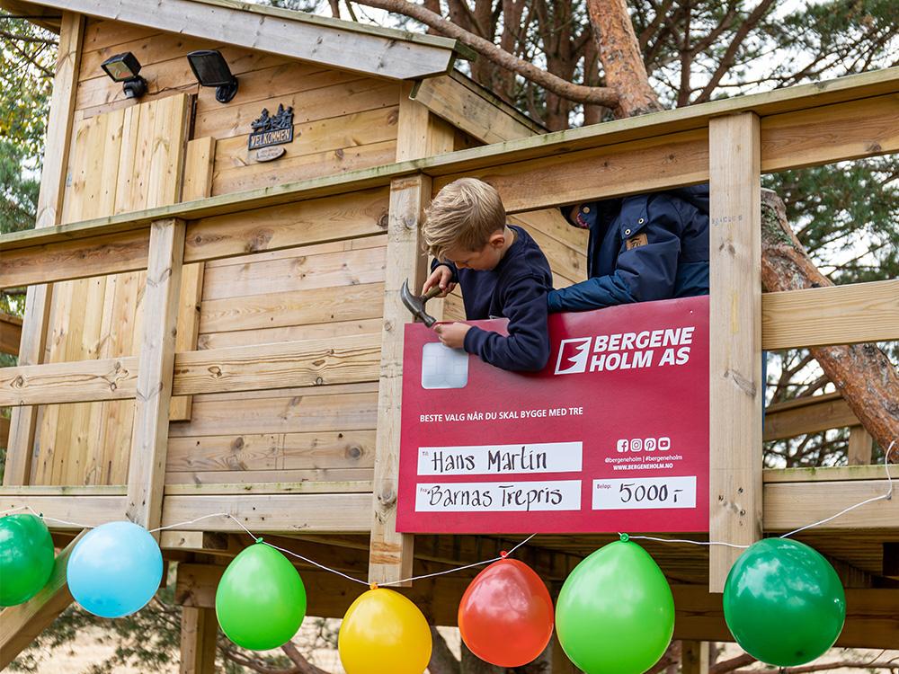 Bilde av Hans Martin som spikrer fast sjekken til trehytta - vinnerinnlegg Barnas Trepris 2020