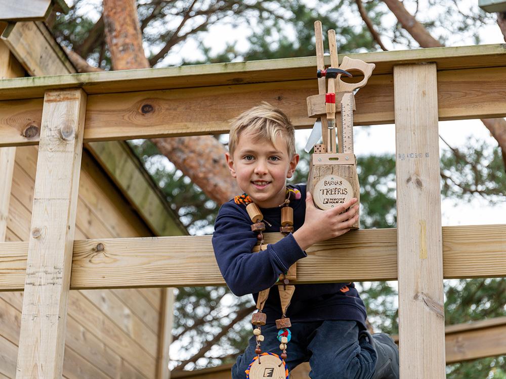 Bilde av prisvinner Hans Martin med vandrerpokal og halskjede tilknyttet Barnas Trepris