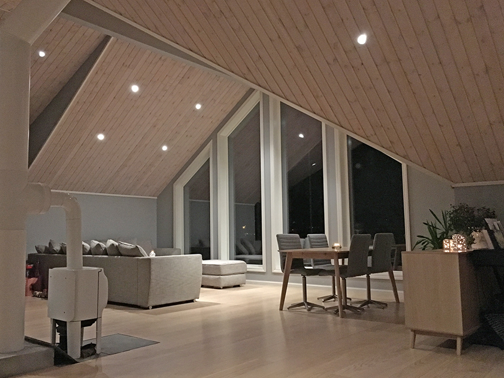 Bilde av stue med høyt og skrått paneltak