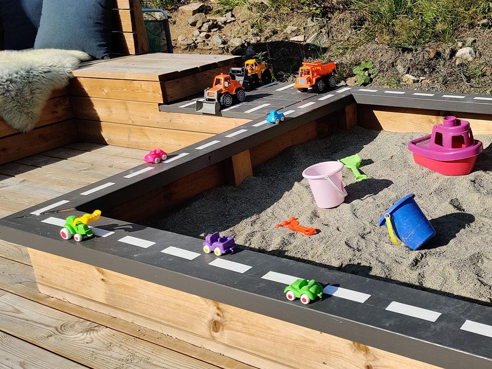 Bilde av aktivitetspark Barnas Trepris 2021. Sandkasse med malt altanrekke.