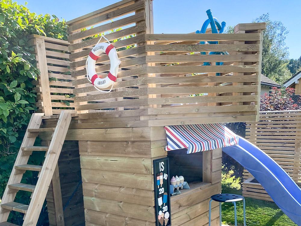 Bilde av kombinert aktivitetsbygg. Finalist i kategori Aktivitetsbygg i Barnas Trepris. Bilde av kiosk og sjørøverskute.