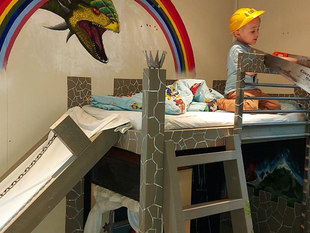 Bilde av køyeseng med drageslott og regnbue. Finalist Barnas Trepris i kategorien kreative barnerom 2021.