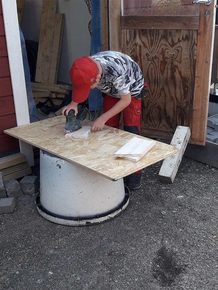 Bilde av snekker som jobber med små byggerier. Finalist nummer 4 i årets Barnas Trepris. Kategori 'Små Byggerier'