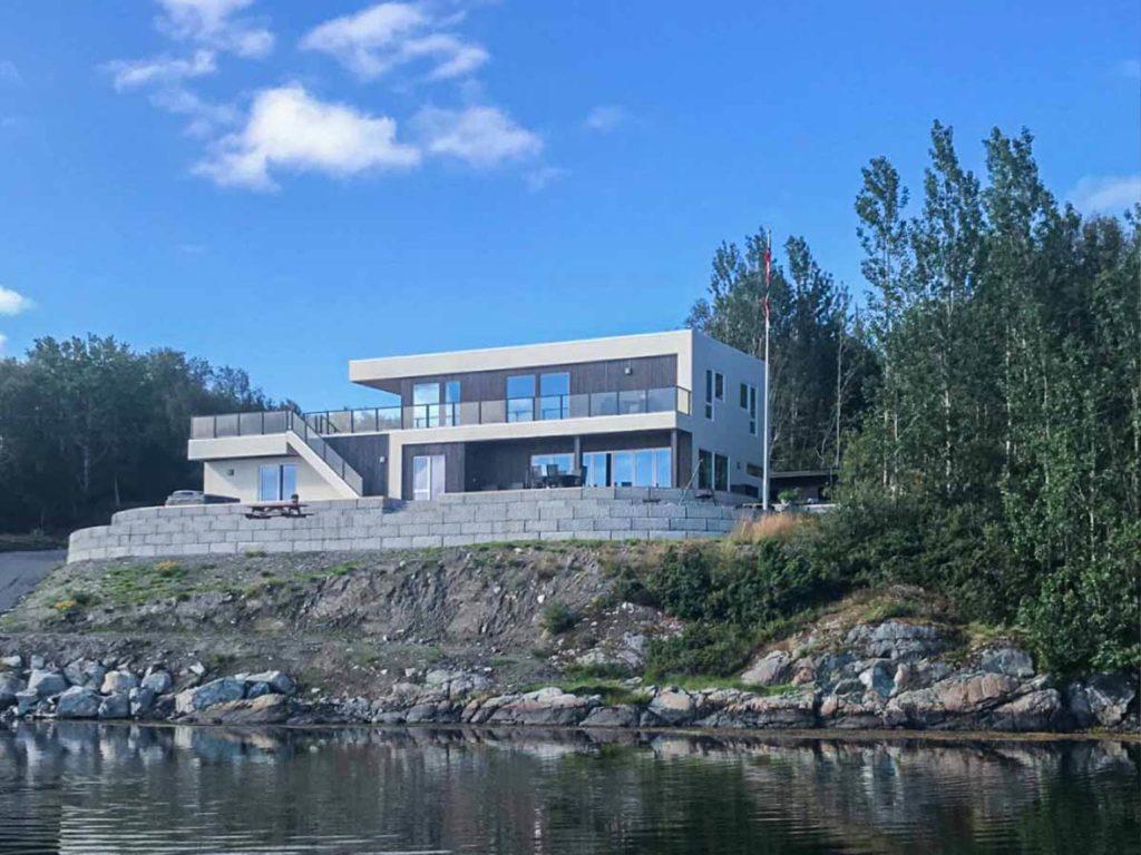 Bilde av moderne hus med NORD-kledning fra vannet. Eksteriørprisen finalist nummer 4 2021.