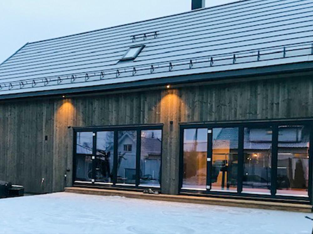 Bilde av huset med store vinduer. Eksteriørprisen 2021 finalist nummer 1.