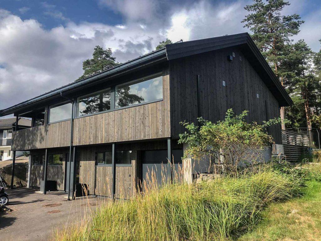 Bilde av hus med Nord-kledning fra forsiden. Bilde av oppkjørsel. Finalist nummer 10 i eksteriørprisen 2021.