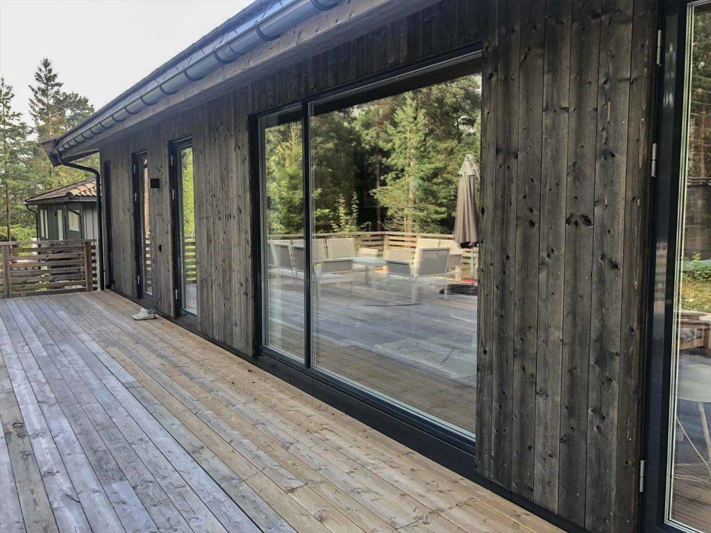 Bilde av hus med NORD-kledning fra baksiden. Terrassebord, NORD-kledning og store vinduer. Finalist nummer 10 i eksteriørprisen 2021.