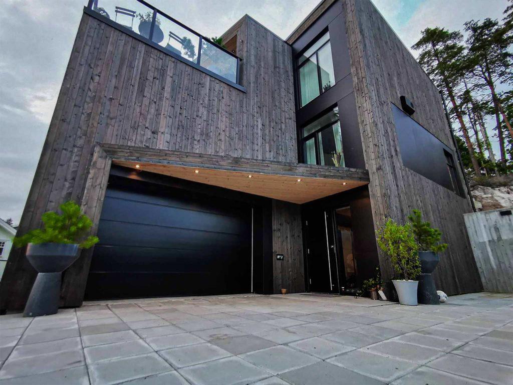 Bilde av hus med Nord-kledning.Garasje og inngangsparti. Finalist nummer 8 i eksteriørprisen 2021.