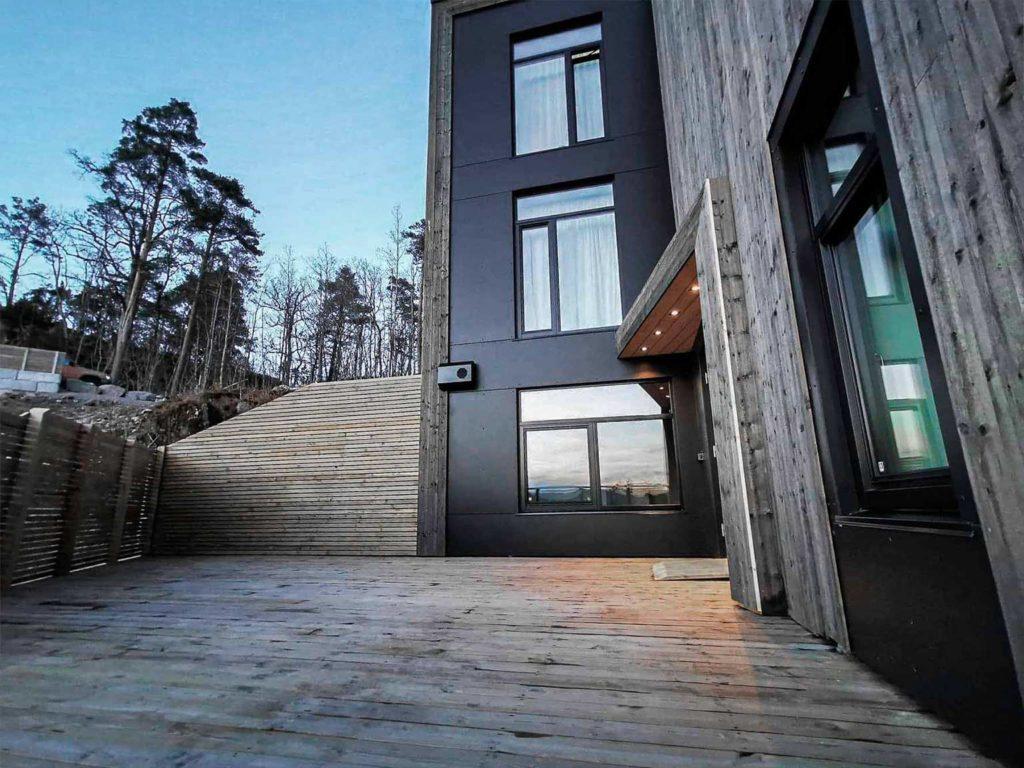Bilde av hus med Nord-kledning. Bilde av terrasse. Finalist nummer 8 i eksteriørprisen 2021.