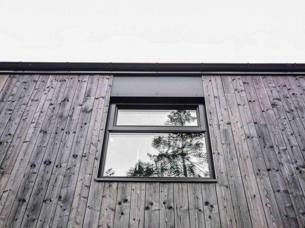 Bilde av hus med Nord-kledning. Vindu med sorte karmer. Finalist nummer 8 i eksteriørprisen 2021.