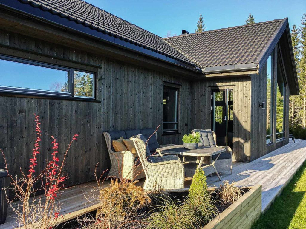 Bilde av hus med NORD kledning og uteromsmøbler - finalist nummer 5 i årets eksteriørpris