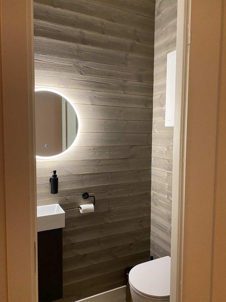 Bilde av toalett med panelvegger - interiørprisfinalist nummer 1 2021.